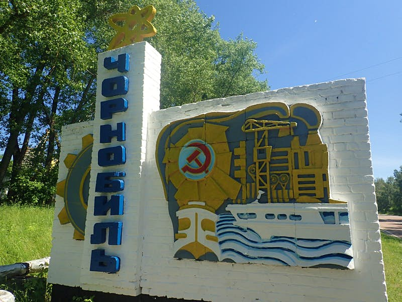 Soviet-era sign outside Chernobyl, with a depiction of the power plant in yellow on a white wall alongside blue script and a red hammer and sickle.