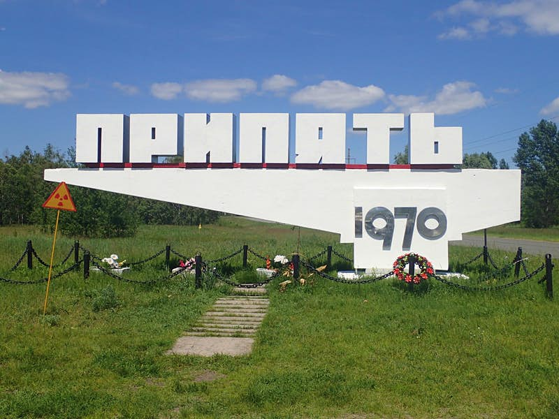 """A concrete sign in Ukrainian script that translates as """"Pripyat 1970"""", when the city was founded; wreaths and flowers are arrayed beneath it and a radiation warning sign stands next to it."""