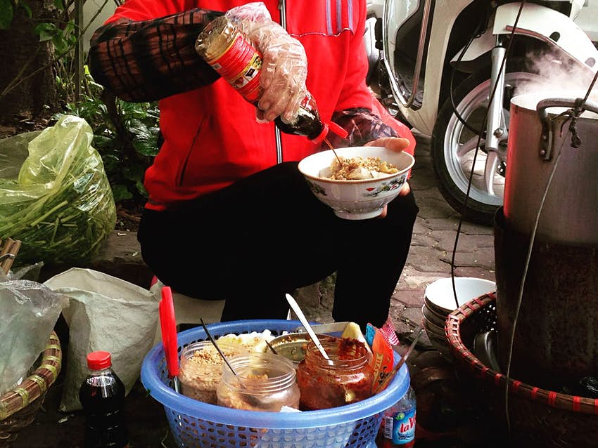 Street food vendor squirts sauce on a bowl of banh da tron