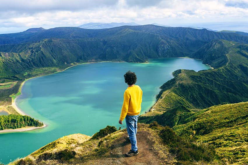 Azores Islands, San Miguel, Man looking at the Lake of Fire, seen from behind.