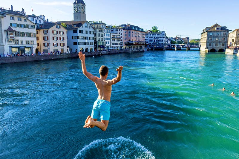 A man jumps into the blue water of the River Limmat in Zurich