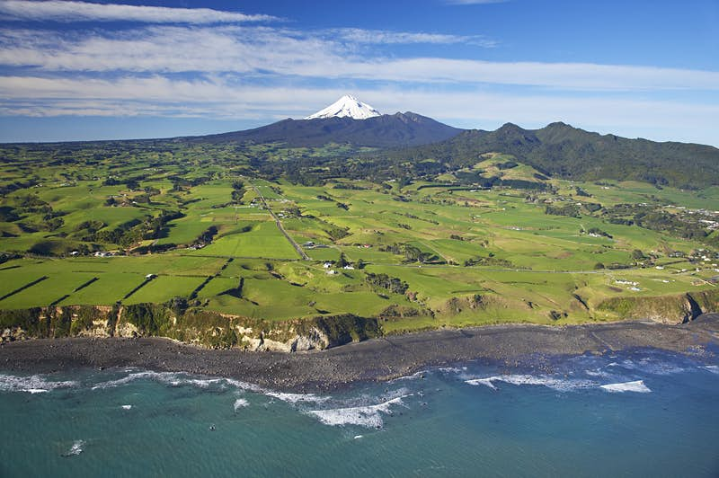 Aerial of Taranaki coastline near New Plymouth with farmland and Mt Taranaki/Mt Egmont in distance. David Wall Photo