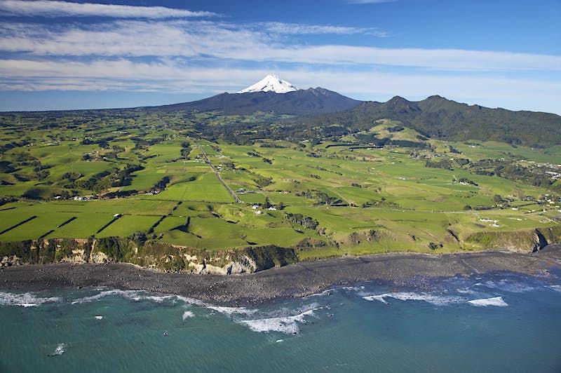 Aerial of Taranaki coastline near New Plymouth with farmland and Mt Taranaki/Mt Egmont in distance. David Wall Photo