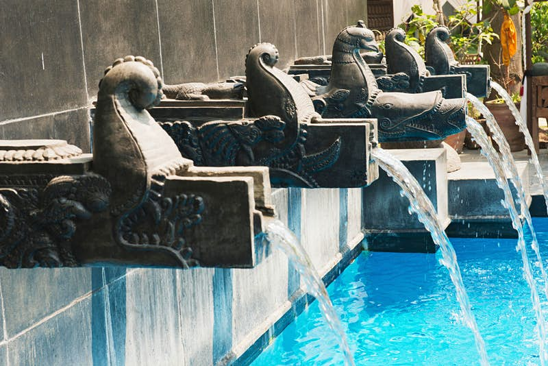 Traditional carved stone dhara (waterspouts) empty into the pool at Dwarika's Hotel © Heather Elton/Getty Images