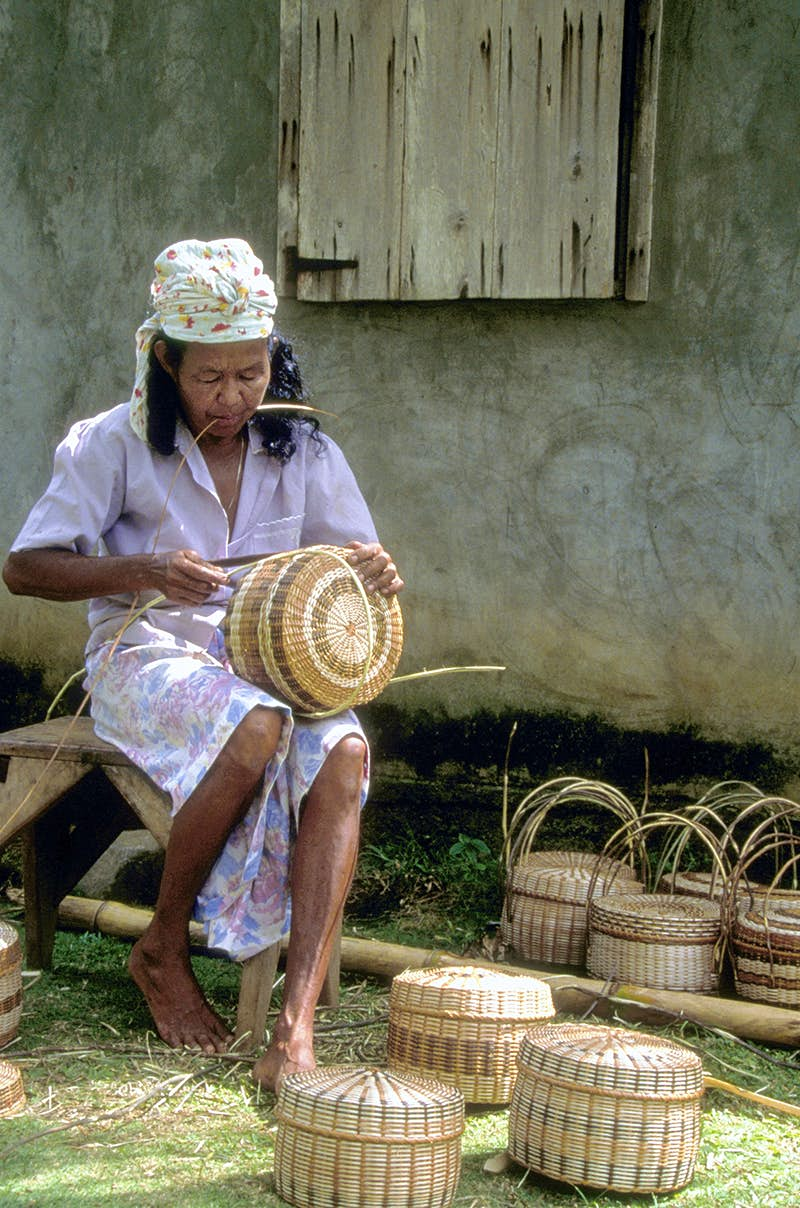 A Kalinago woman weaves baskets © Danita Delimont / Getty Images
