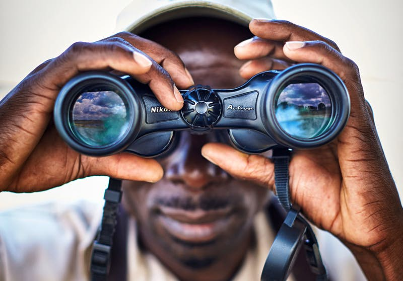 A close up of a guide at Liwonde National Park looking through binoculars