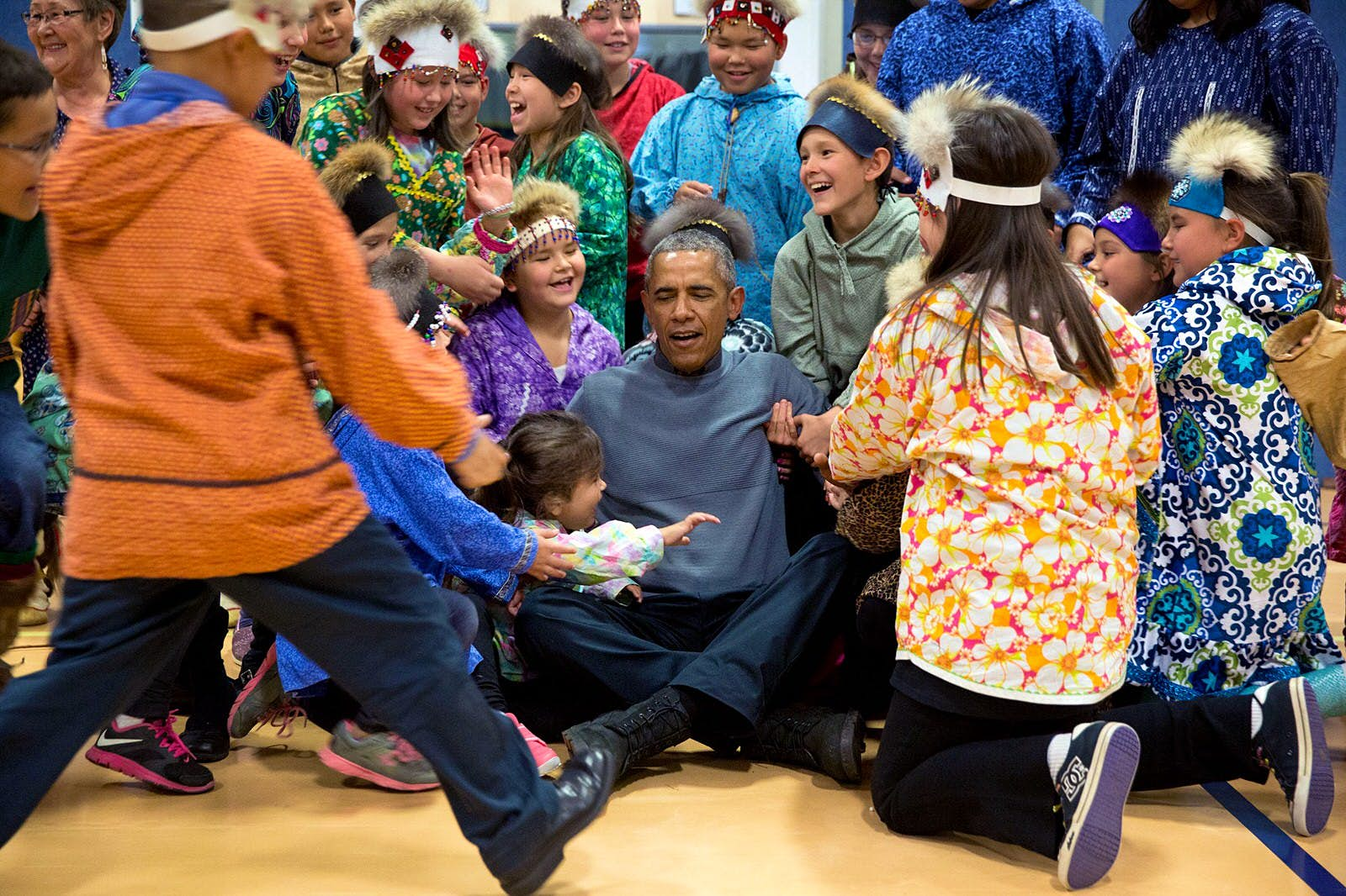 The president being helped to his feet after a group photo with the performers at Dillingham Middle School, Alaska © Pete Souza / Official White House Photo