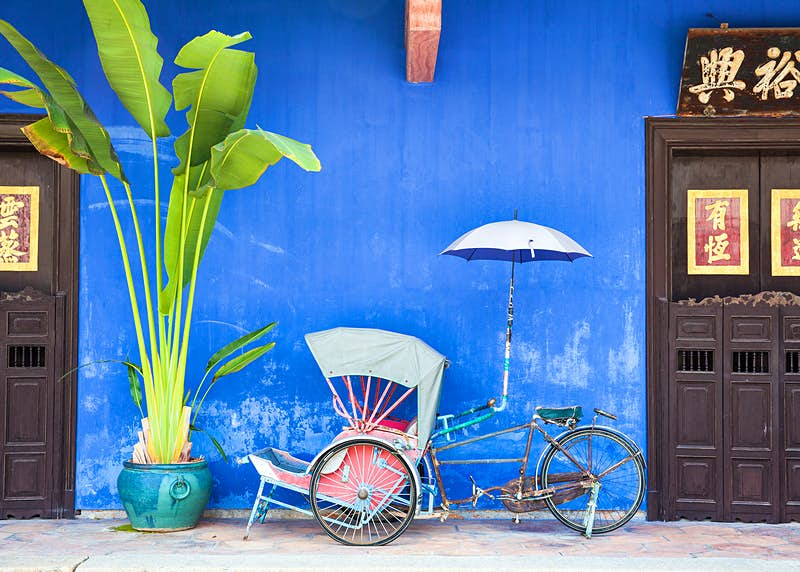 Old rickshaw tricycle near Fatt Tze Mansion or Blue Mansion, a famous oriental historical building in Georgetown, Malaysia © Elena Ermakova / Shutterstock