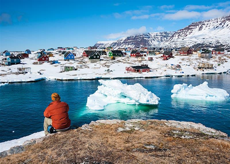 A tourist admiring wonderful views of Qeqertarsuaq, a small town in Greenland © Yongyut Kumsri / Shutterstock