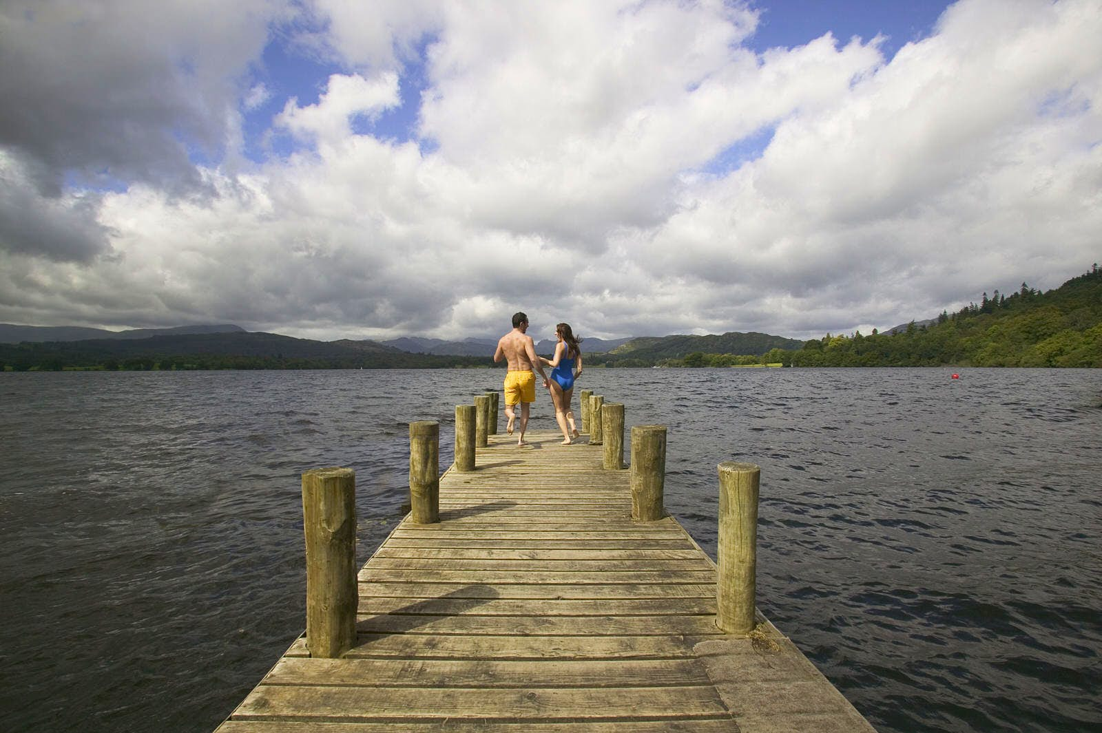 A man and a woman in swimsuits stand at the end of a wooden pier in a lake