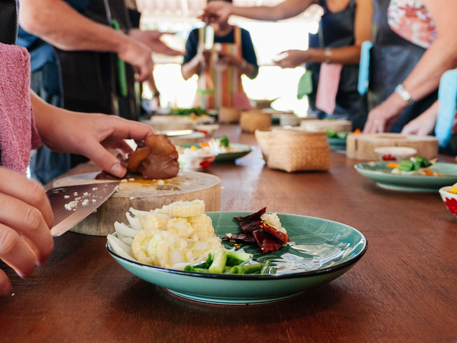 People stand either side of a table, which has a chopping board, ingredients and plates of Thai food
