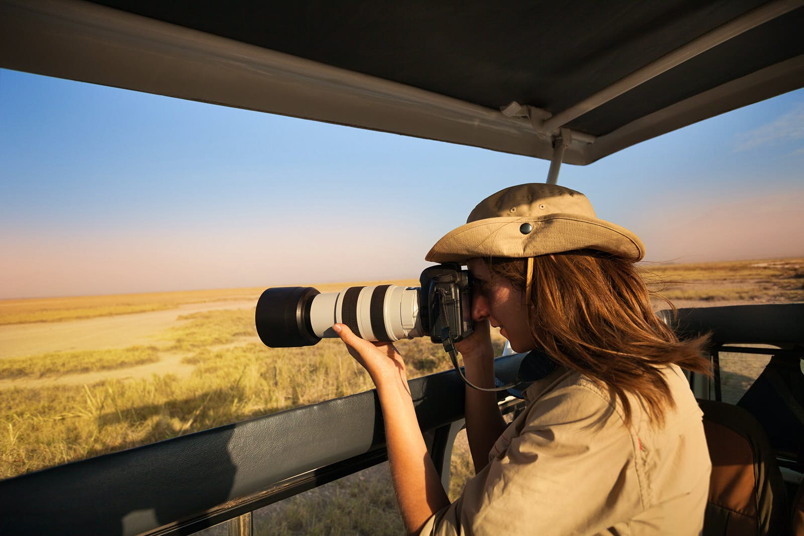 A woman standing on the back of four-wheel-drive looks through a long-lens camera out on to beige and brown grassland