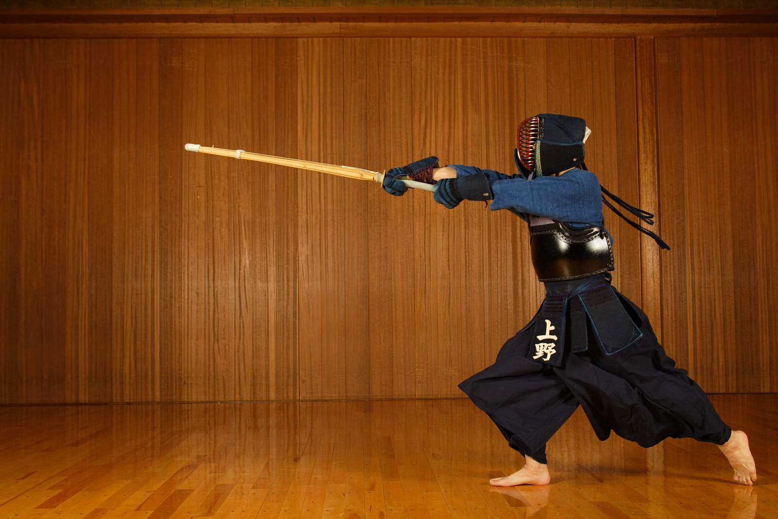 A person dressed in full kendo gear has a fighting stance and holds out the wooden sword