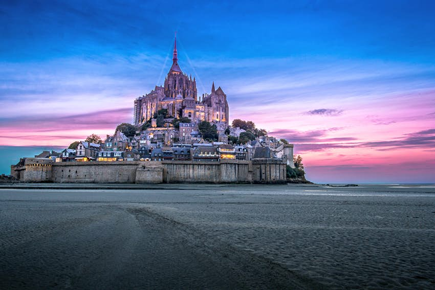 The magical Mont St-Michel abbey against a very dramatic colorful sunset.  The abbey sits on a plain of smooth white sand