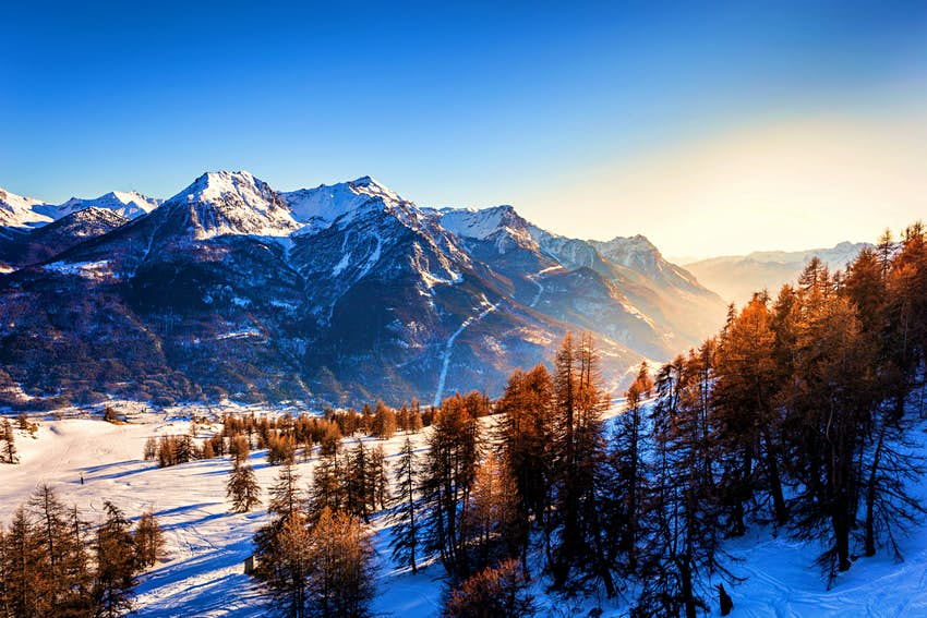 The sun sets over Briançon in the French Alps.  There are sparse evergreens in the foreground, sitting on a blanket of snow, with craggy peaks in the background, crisscrossed with trails