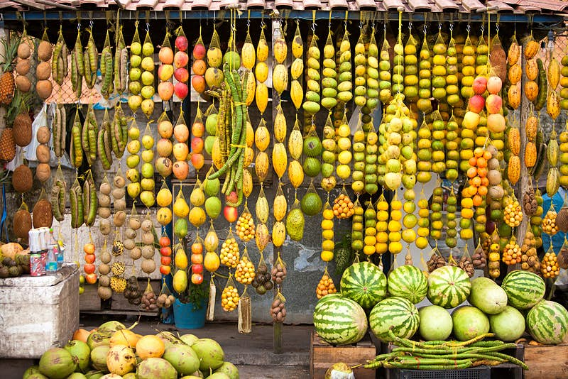 Green, yellow and red fruits hang from the roof of a roadside market in the Amazon. South America.