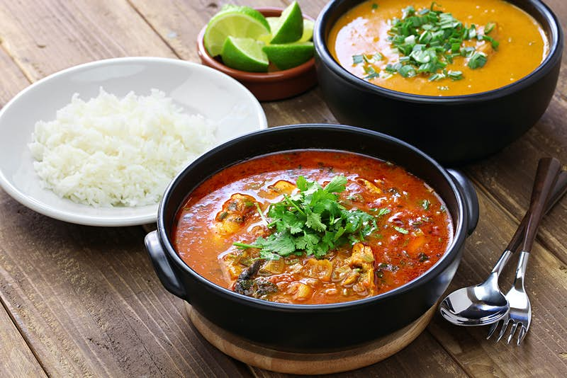A bowl of red stew topped with cilantro sits on a wooden table alongside a plate of rice and a bowl of creamy orange soup. South America.