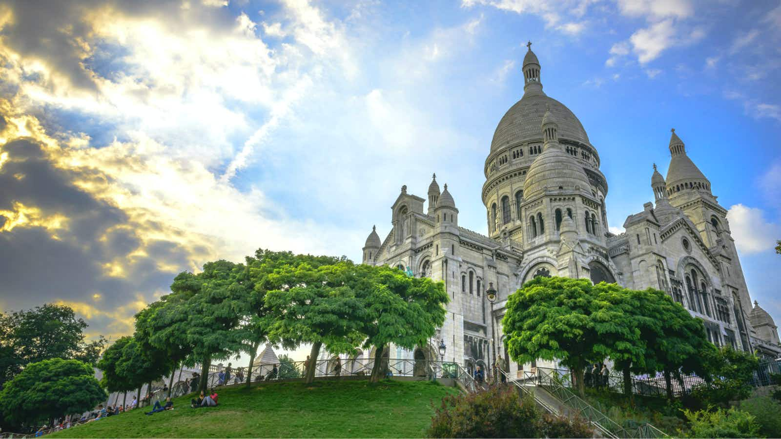 Sacre-Coeur Basilica just before sunset with people sitting on grass in square Louise Michel