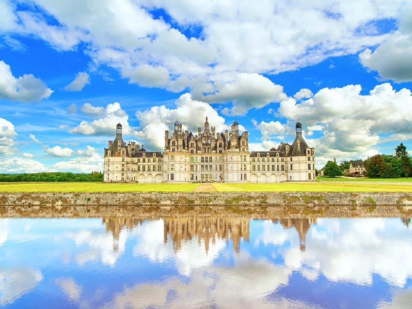 Château de Chambord, imposing Renaissance white brick building with turrets and gray slate roof.  There is a large body of calm water in front of the castle which perfectly reflects the cloudy blue sky above