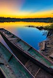 Features - Wooden Canoes Moored On Lake Against Sky During Sunset