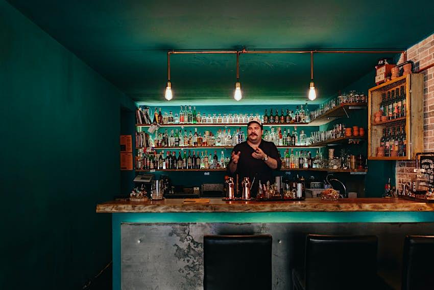 A bartender stands behind the bar at Mad Souls and Spirits, Florence, Italy © Marina Denisova