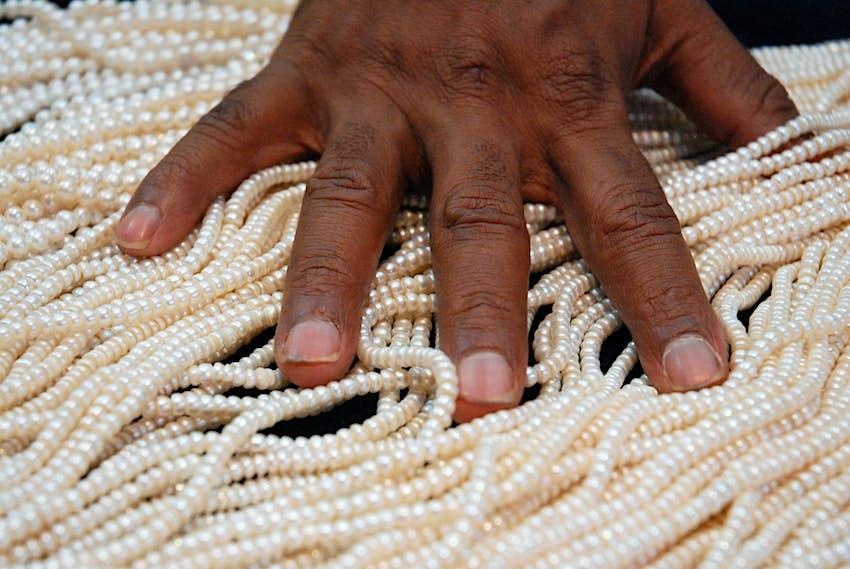 A pearl vendor sorts through strands of Hyderbadi pearls