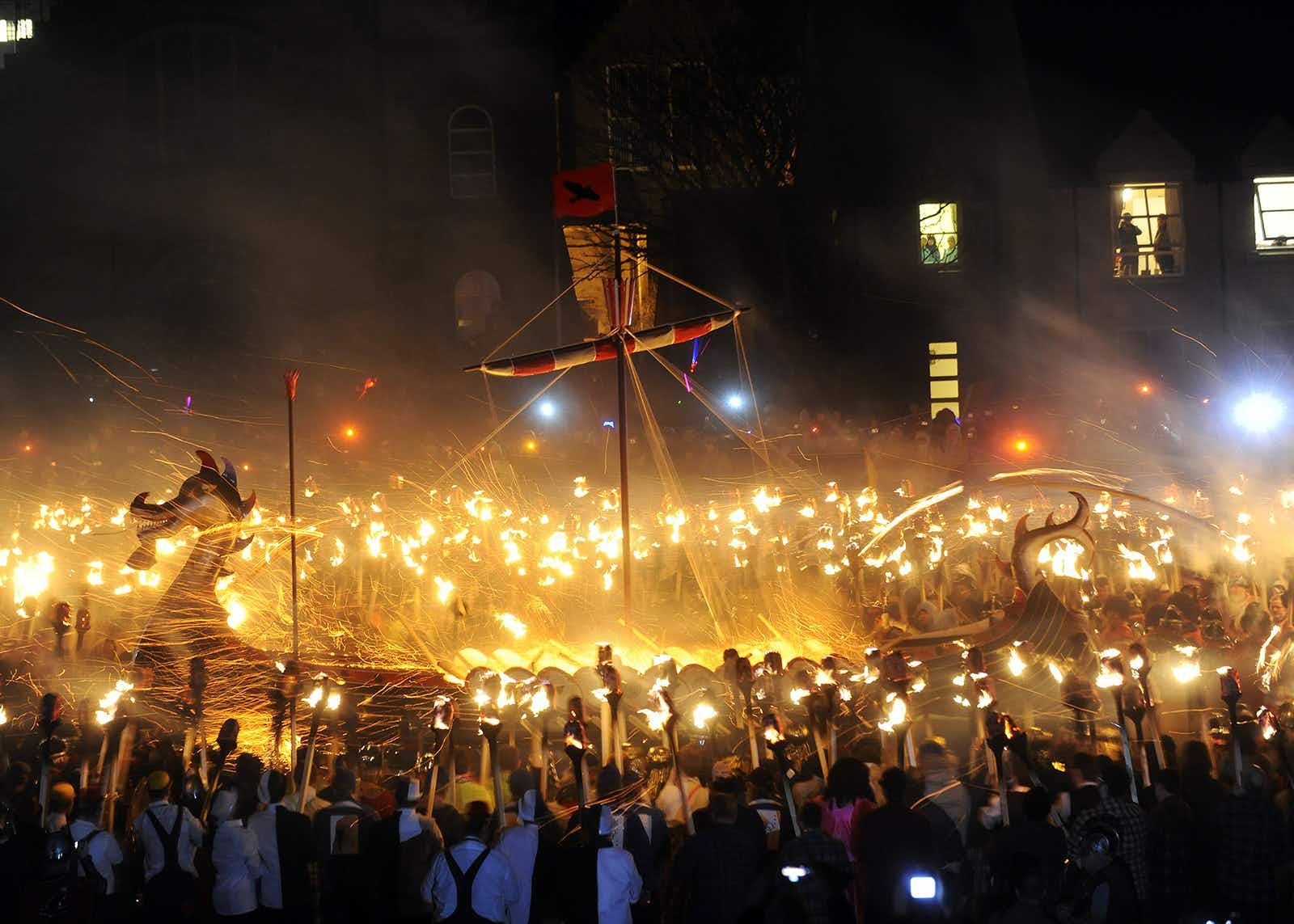 Members of the Viking Jarl Squad surround their leader or 'Guizer Jarl' on a Viking galley ship during the annual Up Helly Aa Festival in the Shetland Islands of Lerwick, on January 31, 2012. Up Helly Aa celebrates the influence of the Scandinavian vikings in the Shetland Islands and has employed this theme in the festival since 1870. The event culminates with up to 1000 'guizers' (men in costume) throwing flaming torches into a Viking longship.  AFP PHOTO / Andy Buchanan (Photo credit should read Andy Buchanan/AFP/Getty Images)
