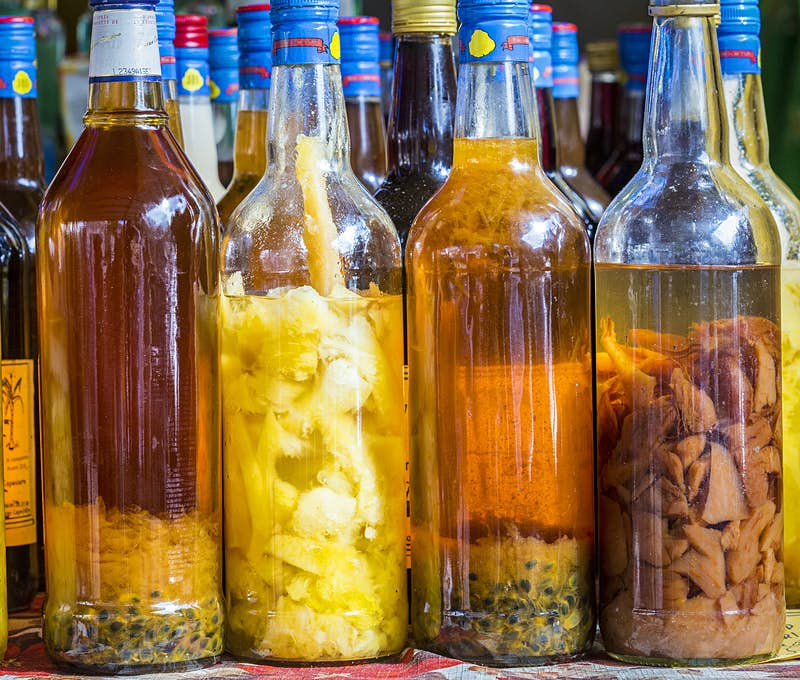 Features - France, Guadeloupe (French West Indies), Marie Galante, Grand Bourg, market stall with local rums arranged (pineapple, passion fruit)