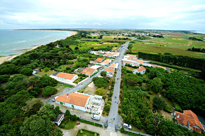 The view from Phare des Baleines lighthouse in Ile de Ré; we see the flat green expanse of the island, studded wityh trees and houses and with a sandy bay curving around the Atlantic Ocean.