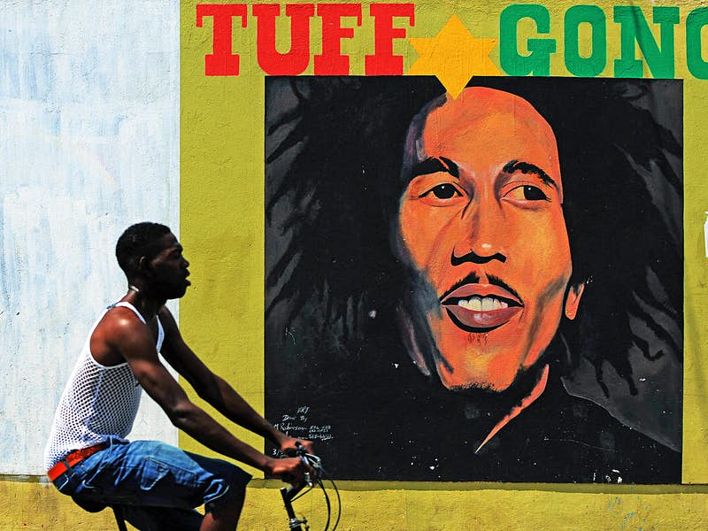 A man cycles past a large mural of Bob Marley on the streets on Kingston, Jamaica