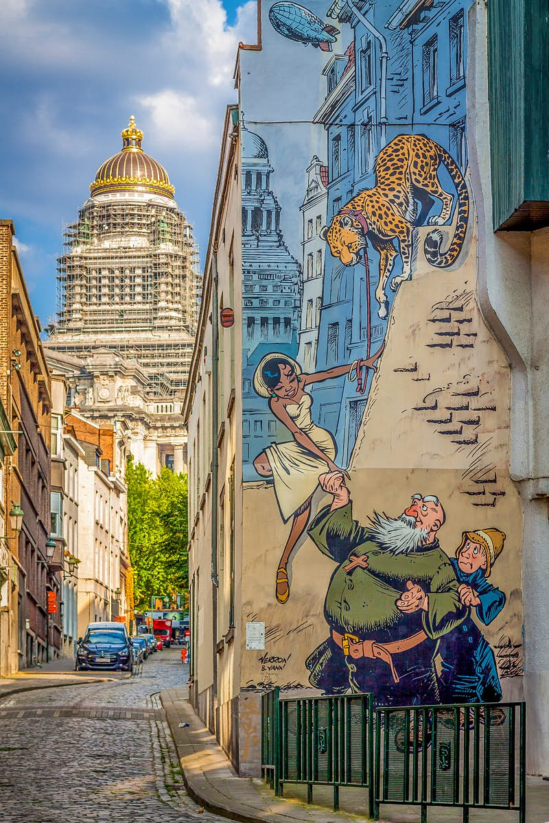 A comic-strip mural of an older man helping a women down a ledge in Brussels city centre