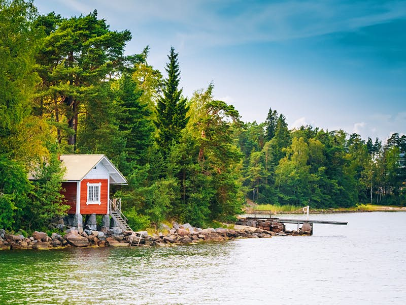 A Finnish sauna nestled amongst a forest on the edge of a lake