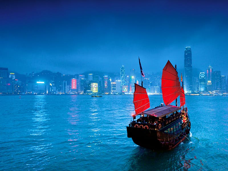 A traditional Chinese junk boat glides across the mist-shrouded Hong Kong harbour