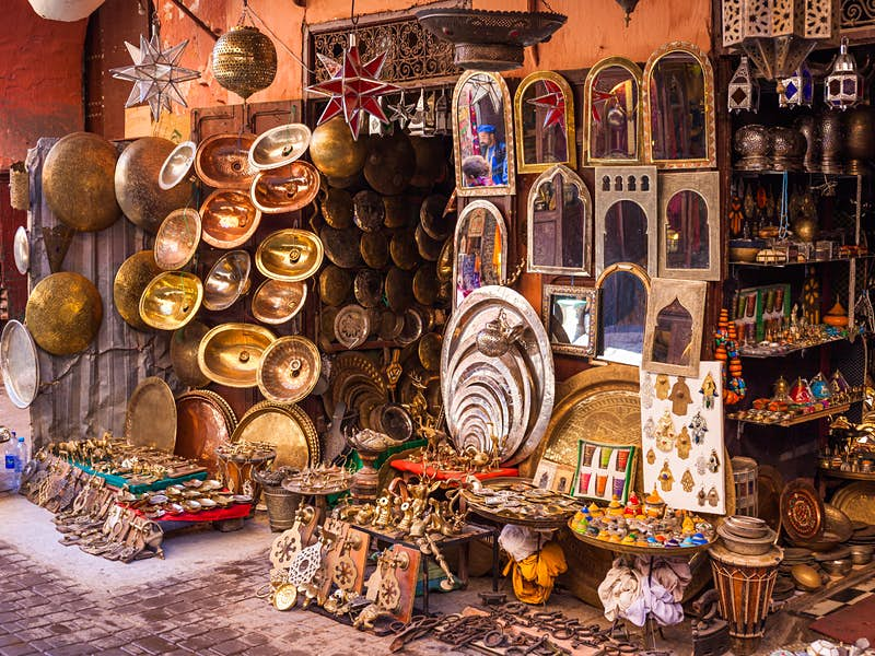 A vendor selling various metalwork items, mirrors and trinkets in a Marrakesh souq
