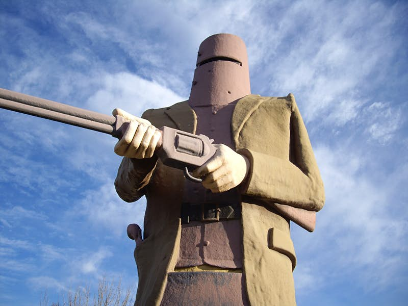 The monument of Ned Kelly wearing his bucket helmet and holding a shot gun at Glenrowan, Australia