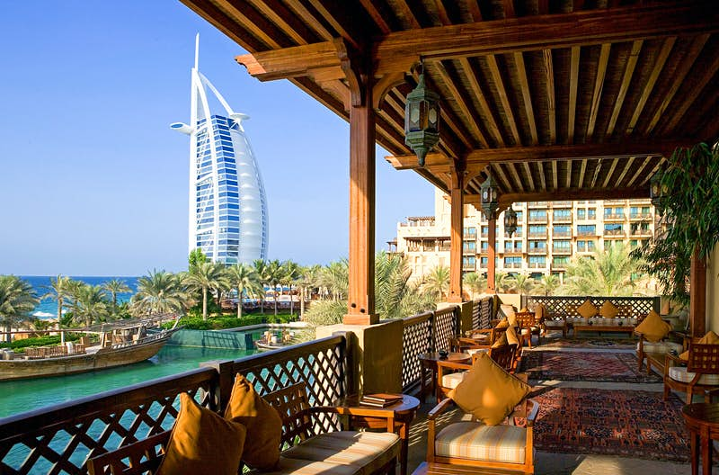 Restaurant with a view of Burj Al Arab in Dubai. The photo is taken from a varnished wooden balcony decorated with woven rugs and wooden, cushioned seats.