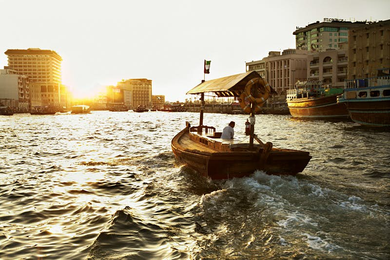 Crossing Dubai Creek on an abra, a traditional wooden boat used to taxi people across the creek. The sun is low on the skyline, and partially obscured by office buildings. A single man is steering the boat and there are no passengers.