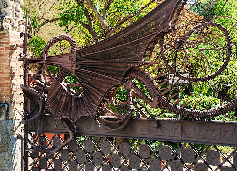 A close-up of Gaudí's intricate, fantastical wrought-iron dragon gate, embellished with likenesses of dragons.