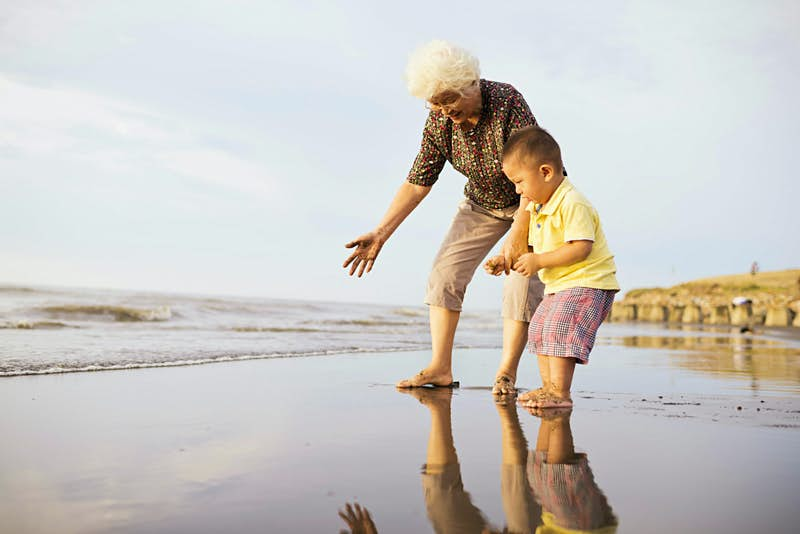 Romantic trip with kids in tow – A grandmother and grandson play on the beach.