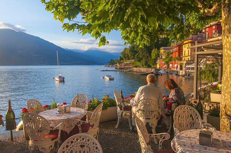 Romantic trip with kids in tow – a couple dine overlooking Lake Como, Italy.