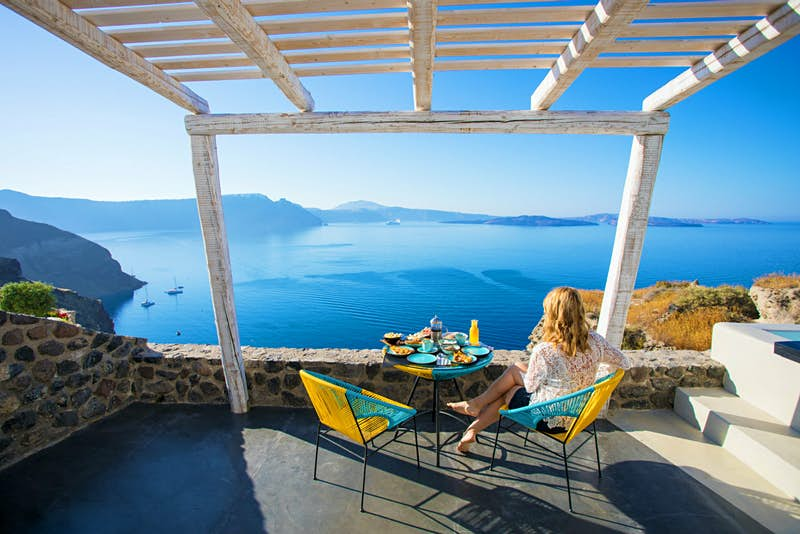 Romantic trip with kids in tow – A woman looks out over the Santorini coastline from the breakfast table.