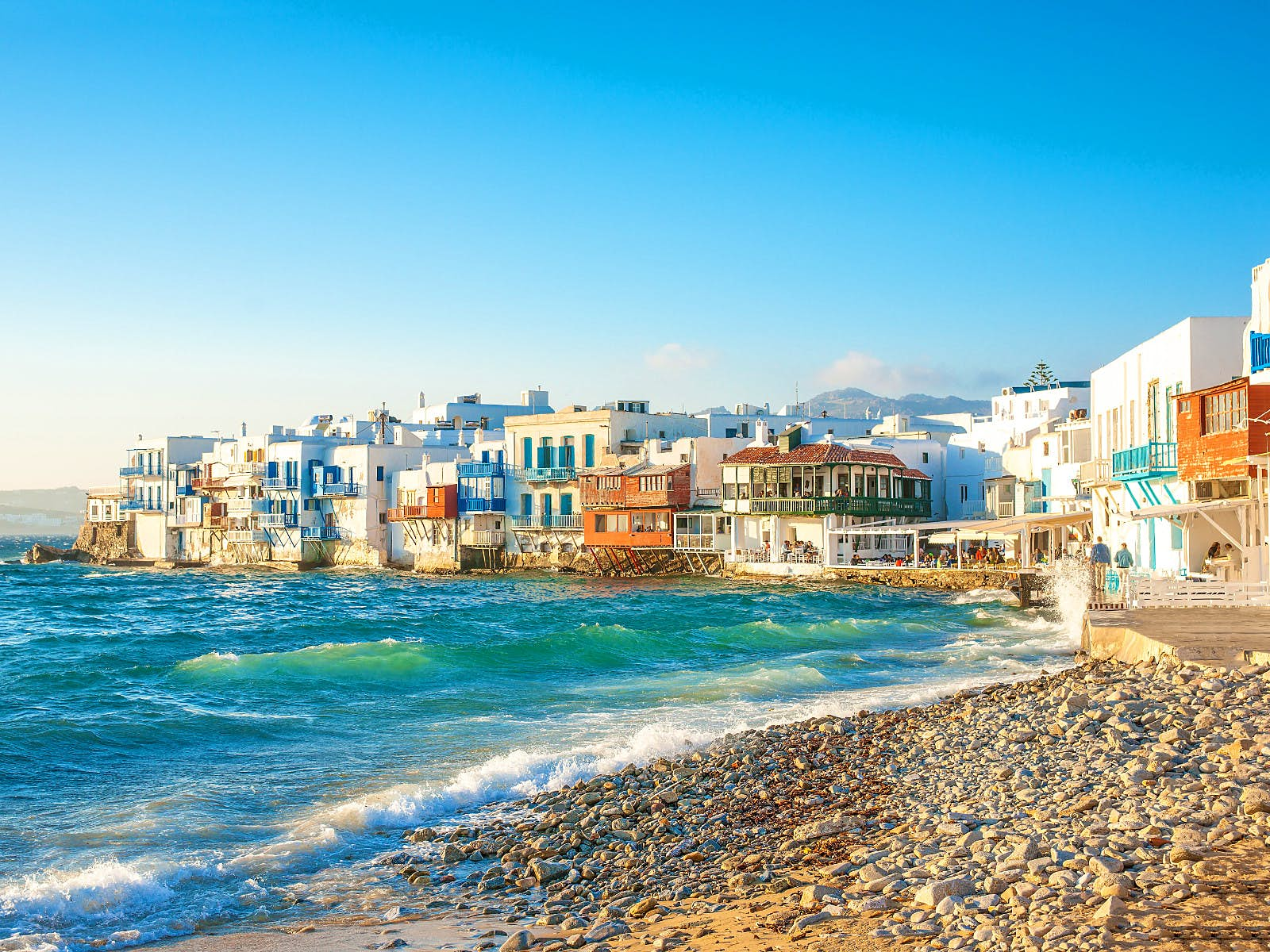 Little Venice Bay in Mykonos. There is a small stony beach in front of a choppy, blue sea. In the background there are white, clue and terracotta buildings, many have wooden balconies propped up on stilts.