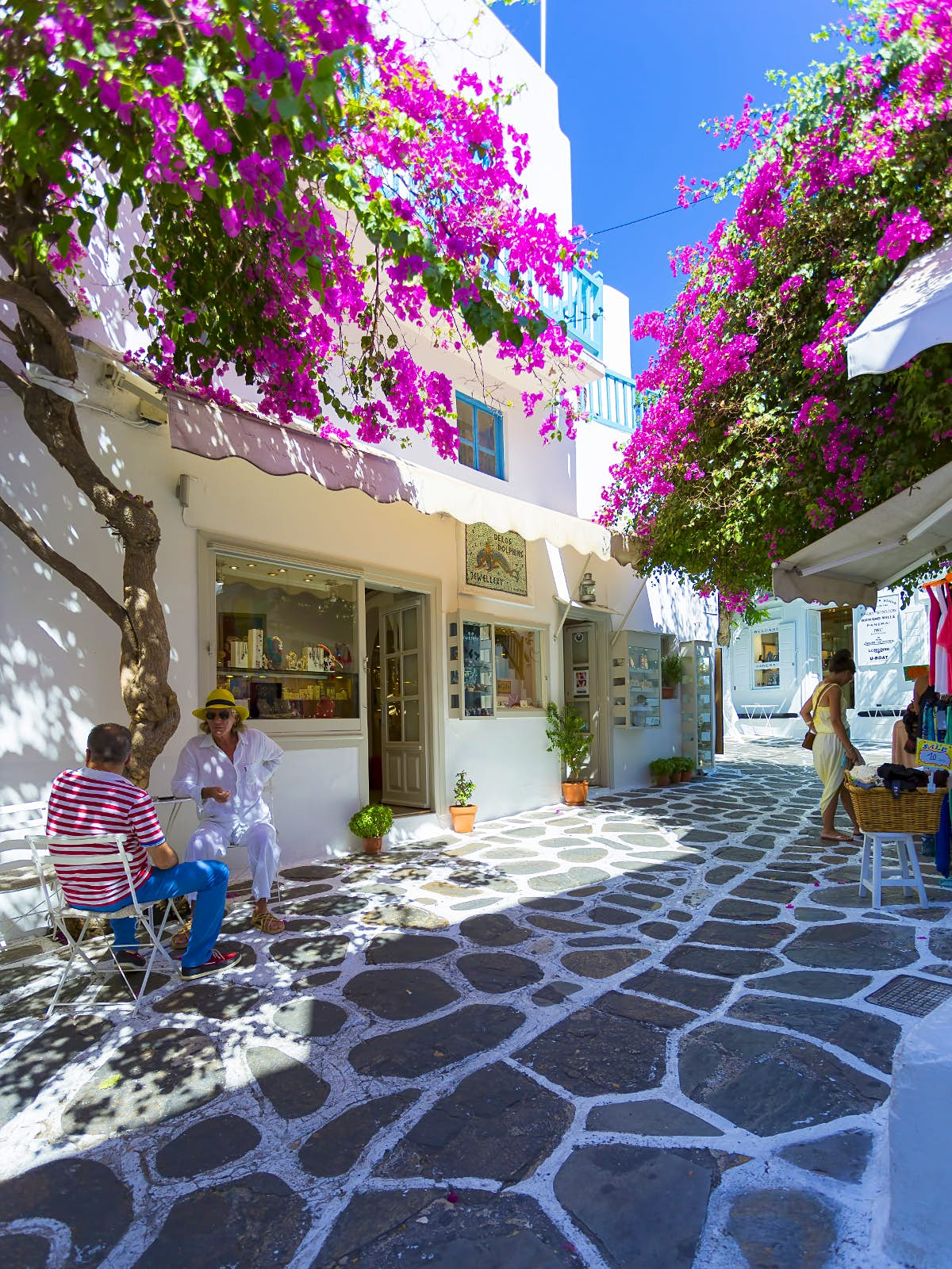 Photo of a small winding stone-paved street lined with purple bougainvillea, shop fronts and small cafes. There are seats outside some of the cafes with people sitting and talking. The sky is completely clear and blue.
