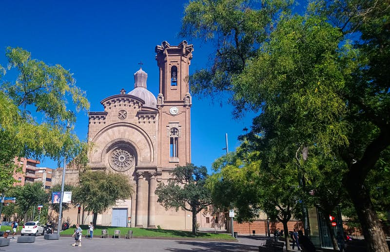 The pink-hued, neo-Gothic Church of Sant Andreu in Barcelona; the church has a tower and a rose window and sits in a leafy square.