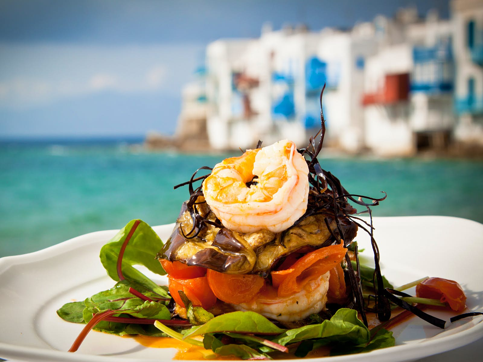 A plate of seafood on a white plate in front of the sea and white buildings which are blurred in the background. On the plate there are king prawns, aubergine, tomatoes, salad leaves and some dressing.