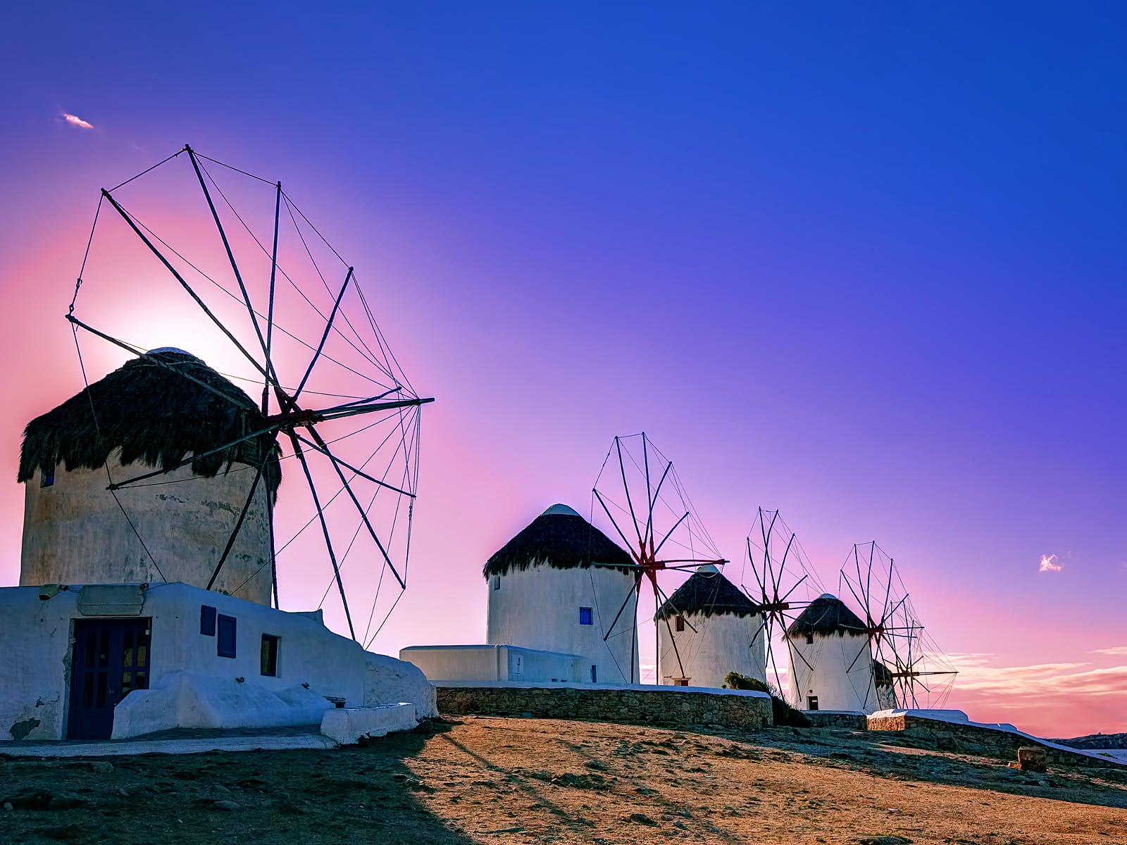 A photo of four short, white round windmills on a small sandy hill. The windmills have thatched roofs and wooden spokes and they are backlit by a stunning pink and purple sunset.