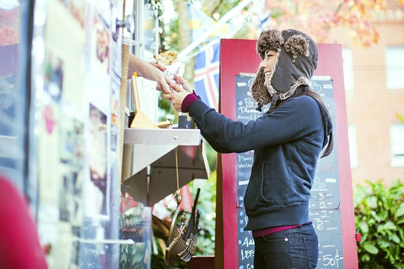 A young woman orders food from a food cart pod in Portland, Oregon.