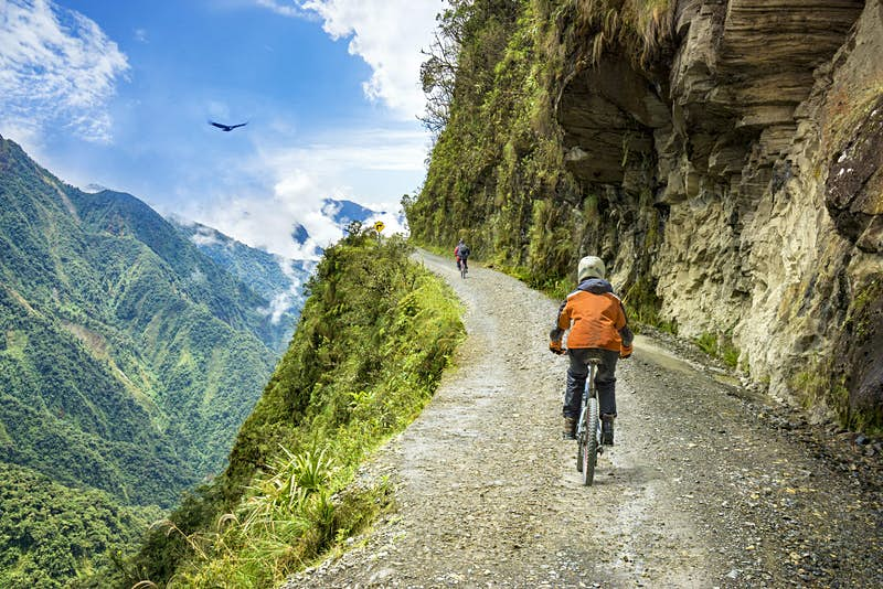 A cyclist rides on Bolivia's Death Road. In the background a condor circles over the scene.
