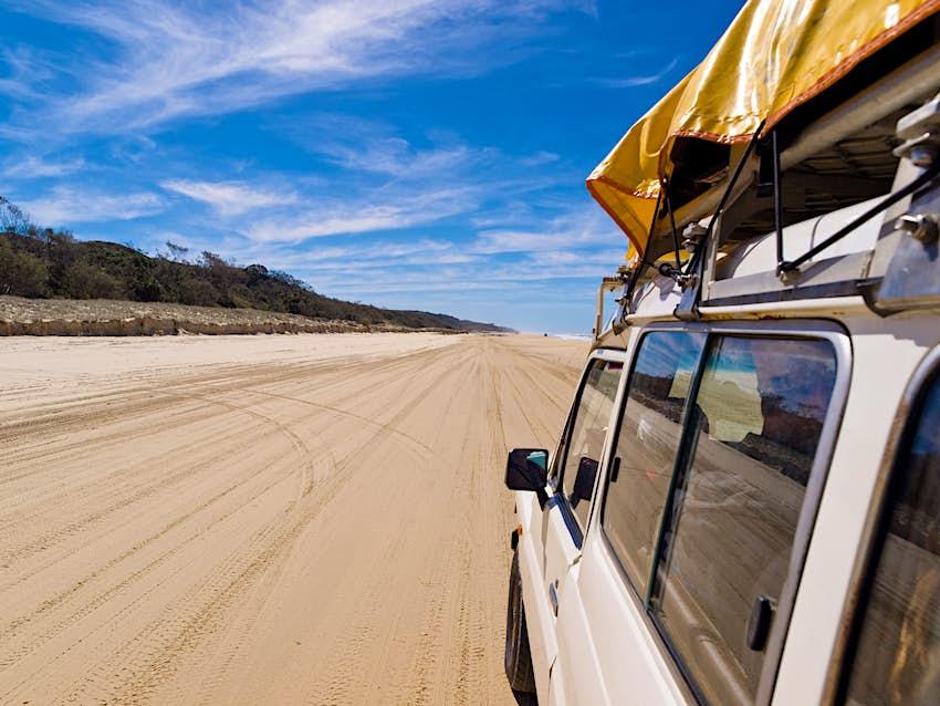 Action shot of car driving along a sandy beach on Fraser Island, Queensland, Australia