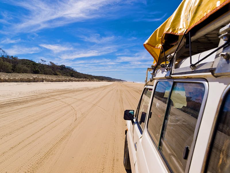 Action shot of car driving along a sandy beach on Fraser Island, Queensland, Australia